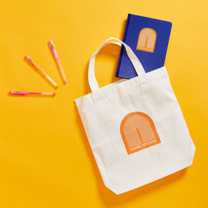 give a custom tote bag, journal and pins to the client on the go