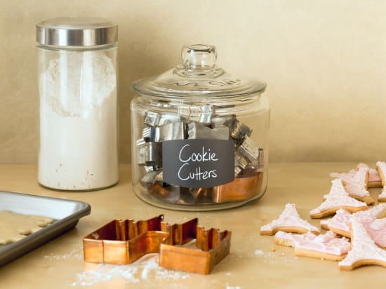 Display similar items, such as clunky cookie cutters, using apothecary jars and chalkboard labels.