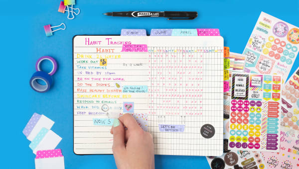 blue table surface with various avery office supplies and open habit tracker with colored text and ultra tabs