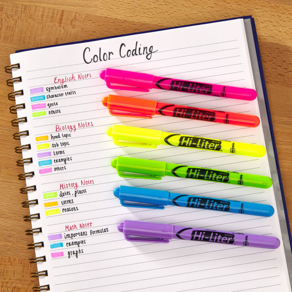 multiple neon highlighters in spiral bound notebook