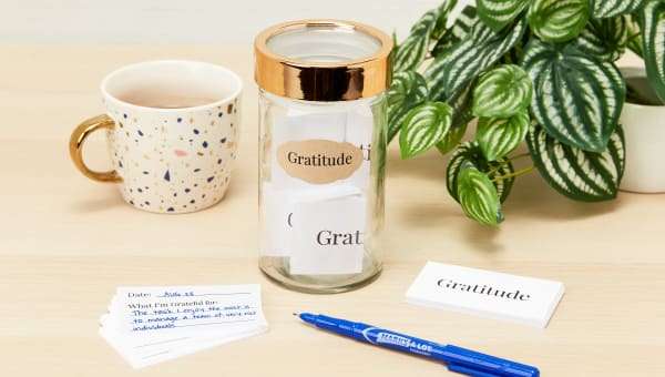A glass gratitude jar filled with slips of paper with positive messages and appreciative thoughts sitting on a wood desk