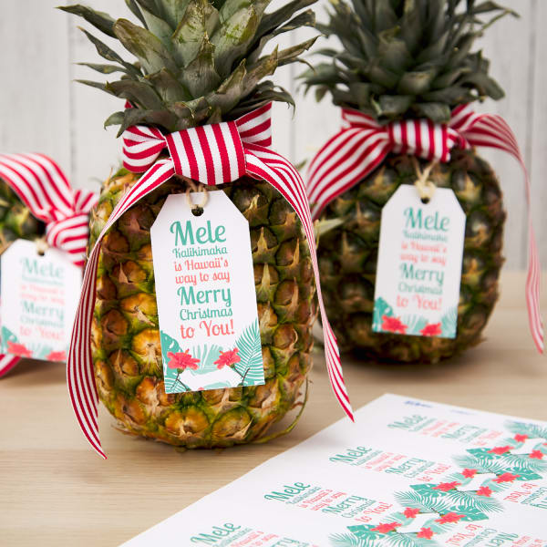 pinapples with festive holiday tags next to sheet of Avery tags