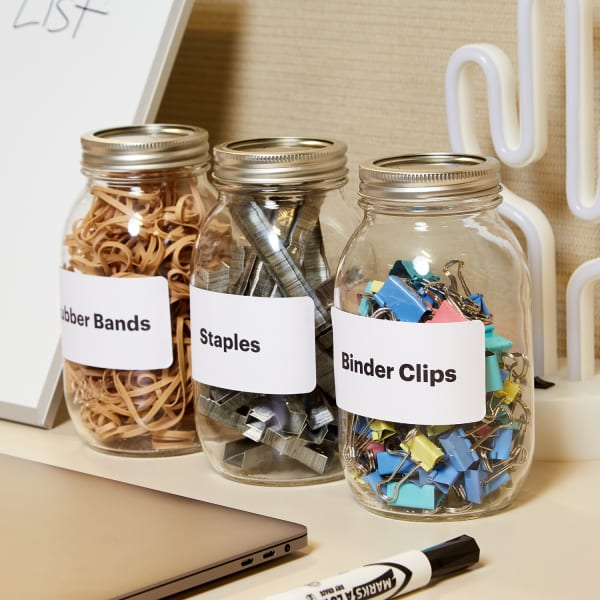 close up of a neat and tidy desk with labeled mason jars for office organization and other work items including a laptop marker white board and decorative cactus lamp