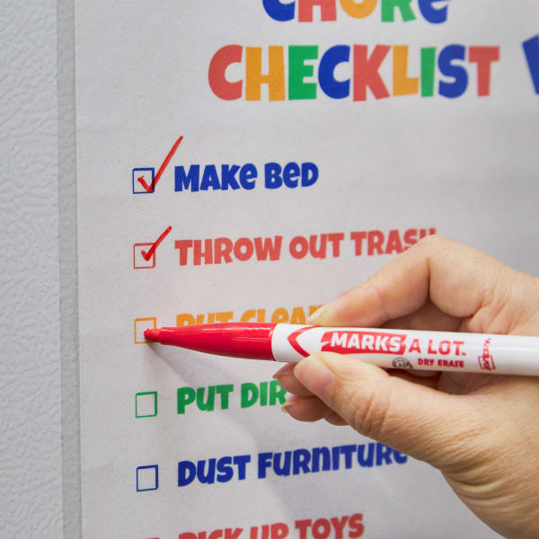 close up of colorful kids chore chart with items being marked off as part of a family cleaning schedule