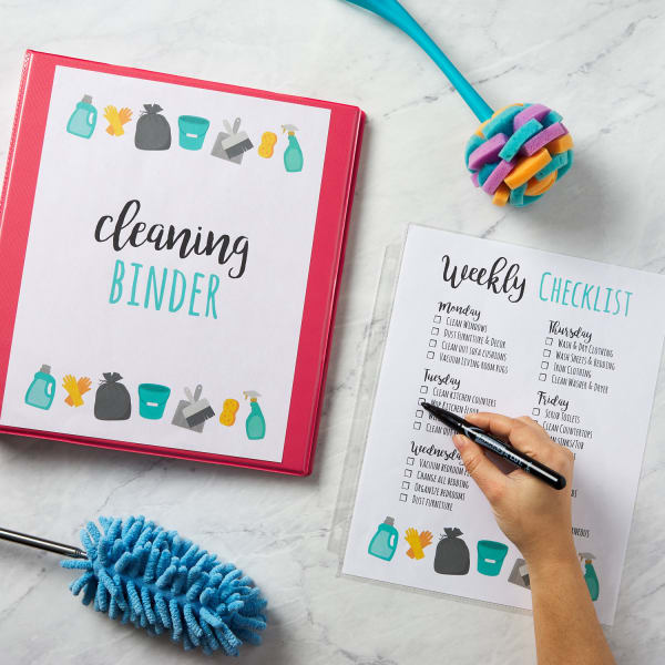 cute cleaning schedule template for a weekly checklist and cleaning binder on marble countertop with supplies and tasks being marked off