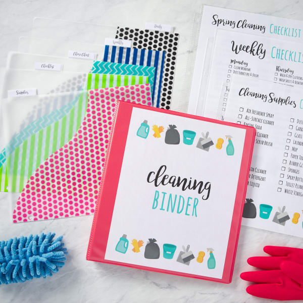 colorful cleaning schedule binder cleaning checklists dividers and cleaning supplies arranged artistically on a marble countertop