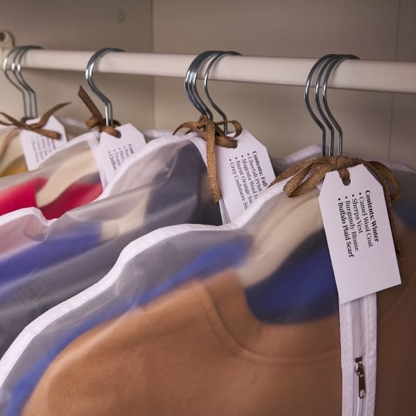 several clothing items on hangers in closet labeled with printable tags