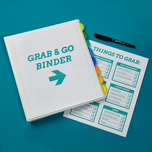 closed emergency binder and divider set on blue table