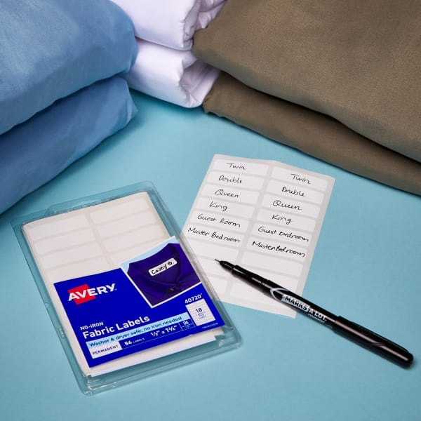 set of no-iron fabric labels in packaging next to various blankets and sheets