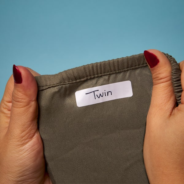 hands holding up brown sheet with no-iron fabirc label attached