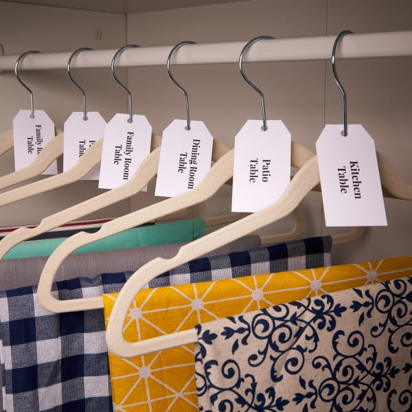 closet filled with tablcloths neatly organized on hangers and tagged with prepunched tags
