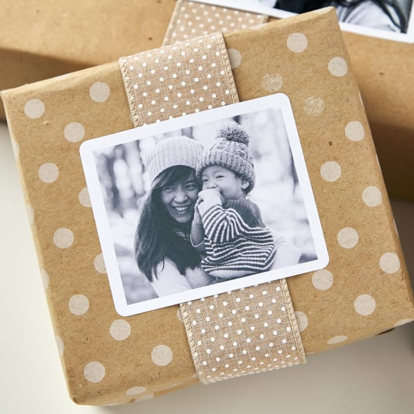 polka dot kraft brown paper wrapped around a gift boxes tied with fabric ribbon and topped with personal black and white photo