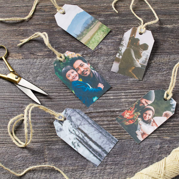 five beautifully printed to the edge family photos on gift tags with twine ties on wooden table next to gold scissors