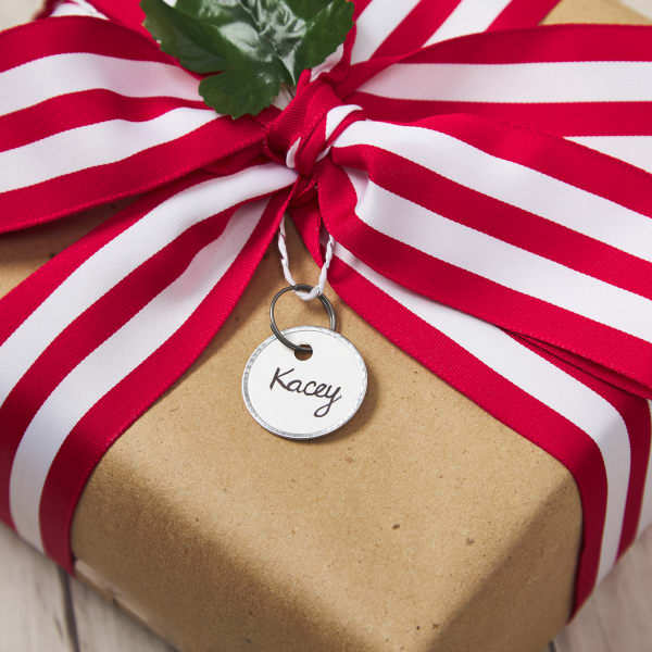 gift wrapped with plain kraft brown paper, tied with large red and white striped bow and tagged with minimalist metal rim tag