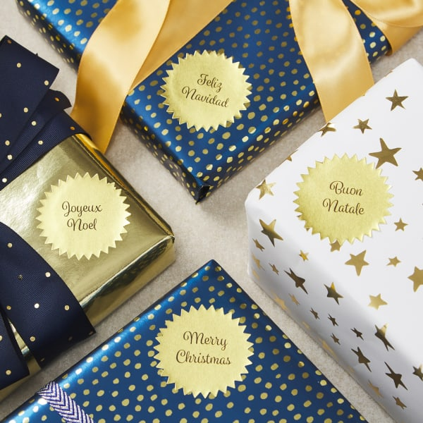 gold metallic starburst labels  with text on four wrapped Christmas presents with star and polka dot metallic wrapping paper