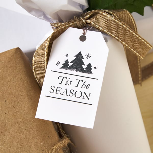 clean white gift tag with Christmas pine tree design on bottle wrapped in white wrapping paper and tied with burlap and white ribbon