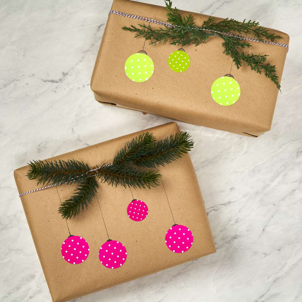 handmade ornament themed gift wrapping paper made with colorful round labels on craft brown paper and handdrawn lines, with pine branches tied around