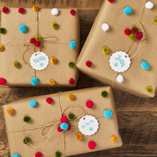 three craft brown paper wrapped holiday gifts tied with burlap string and decorated with small, colorful pom poms and tagged with small round scallop tags