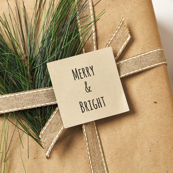 craft brown paper gift box tied with burlap ribbon and real pine branch and topped with kraft brown square labels