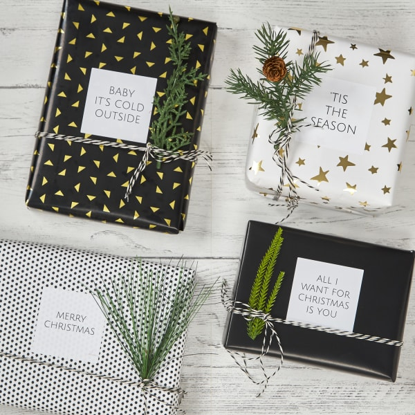 large white square labels on four gifts wrapped in black, white, and gold wrapping paper
