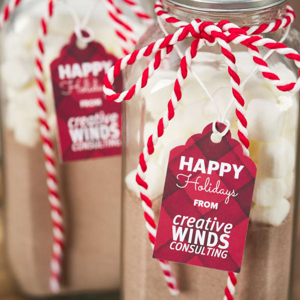 close up shot personalized hot chocolate mix gifts with festive red and white holiday ribbon and custom holiday tags