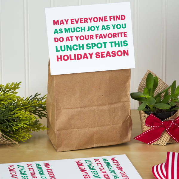 paper lunch bag topped with large postcard label with festive holiday message on table