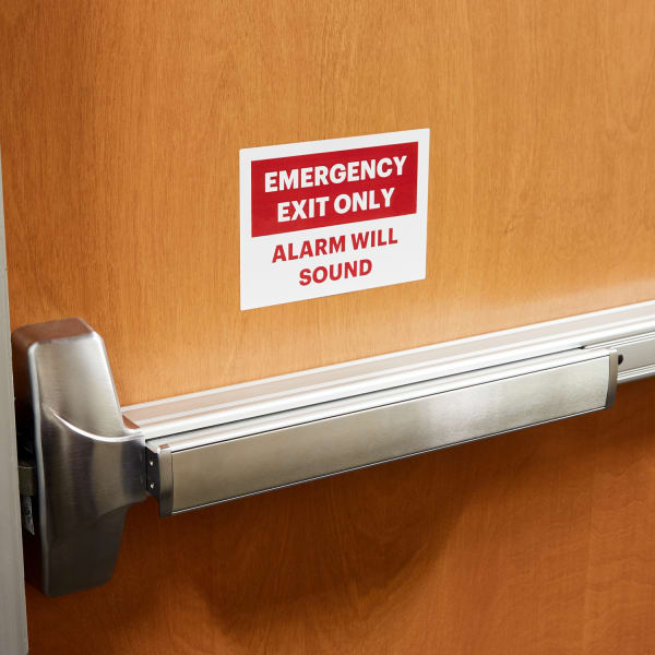 red and white self adhesive emergency exit office sign applied on a wooden door