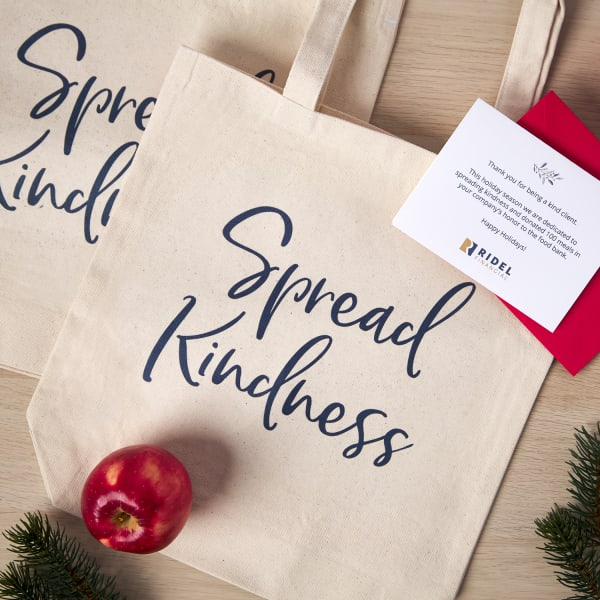client appreciation gift custom tote bag arranged on wooden pine table with apples and holiday greenery
