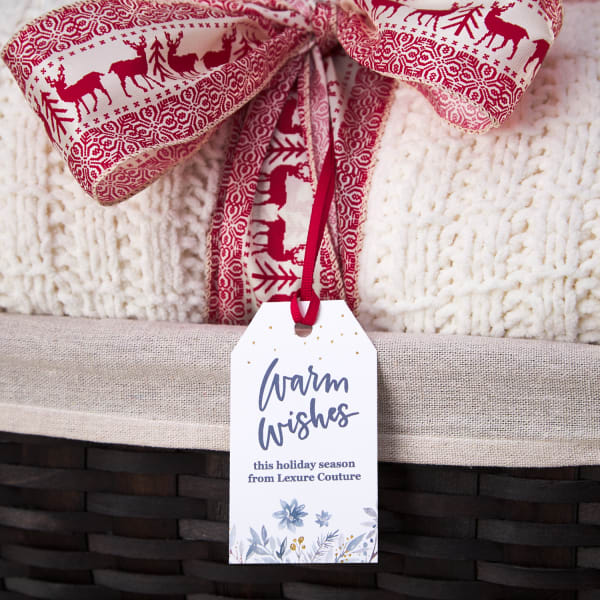 cozy blanket client gift tucked in a nice wicker basket with red deer print ribbon and a custom hang tag