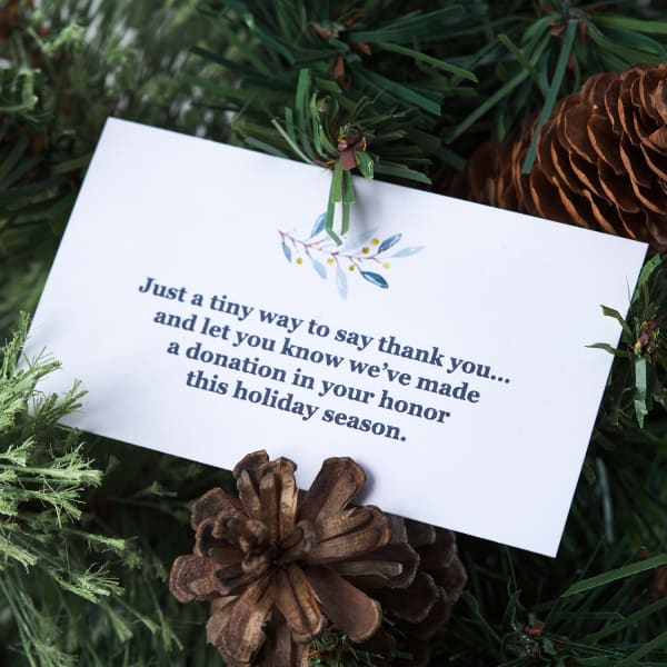 diy donation message for customer appreciation gifting nestled in pine branches with pine cones