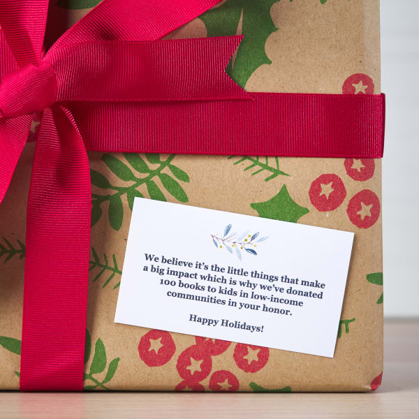 red and green natural holiday theme gift wrapped customer appreciation gift with large red bow and personalized message