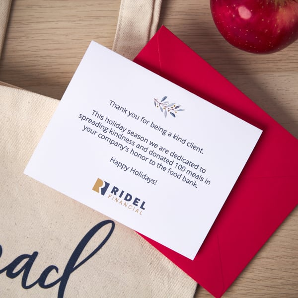 close up of a diy printable appreciation gift card with a tote bag and apples arranged on a light pine wood table with a holiday theme