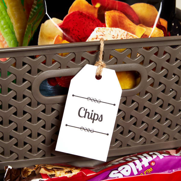close up of a brown woven plastic snack bin filled with chips and labeled with printed tag