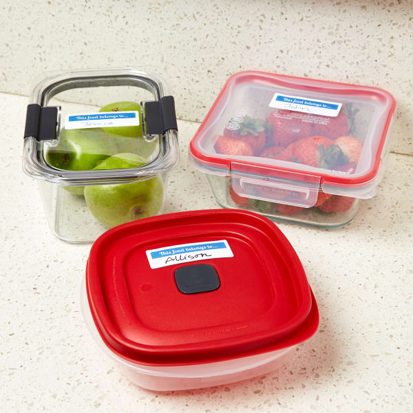 apples and strawberries in employee lunch containers with avery labels on a white and grey kitchen counter