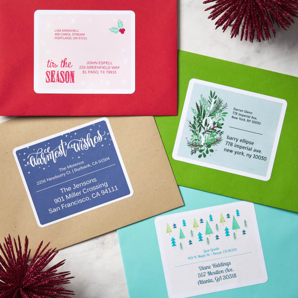 four colorful envelopes with large Christmas labels on table