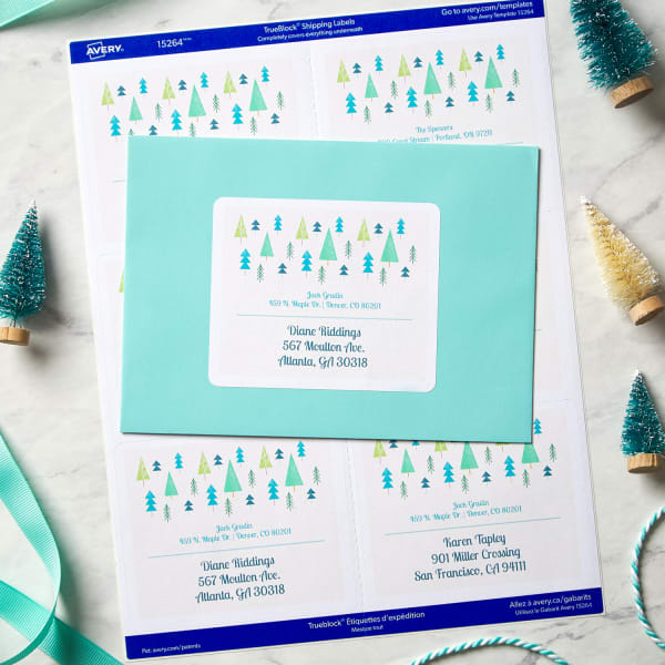 Light blue envelope with large label decorated with adorable small Christmas tree illustrations sitting on top of a sheet of Sure Feed labels of same design