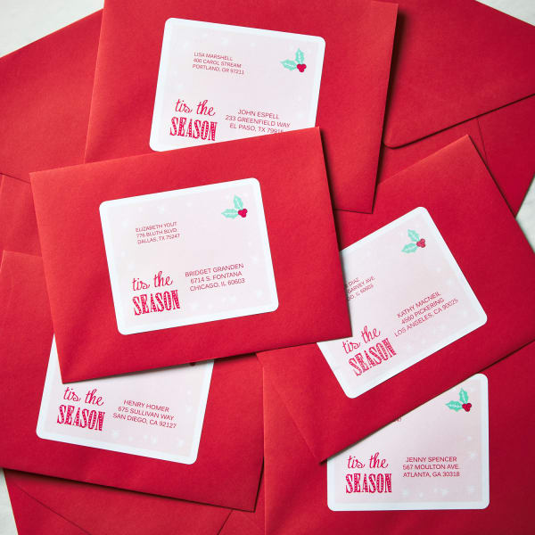pile of red envelopes with large rectangle Christmas themed labels on table
