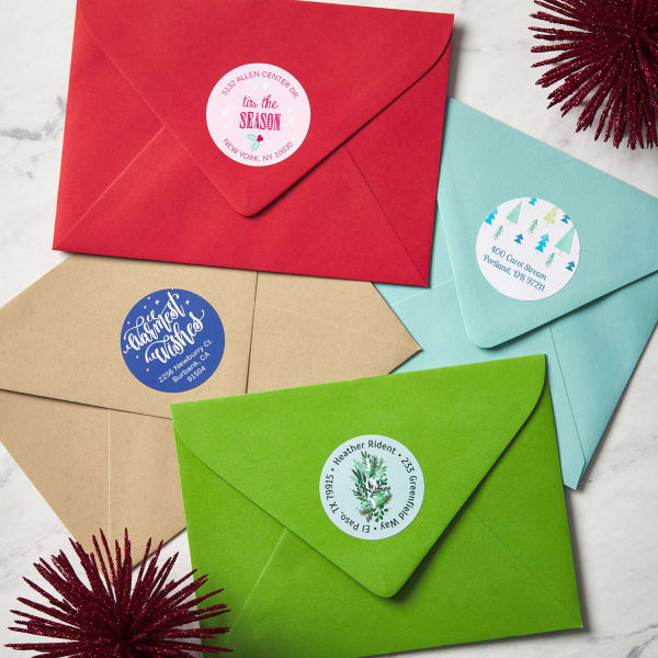 four colorful envelopes facing upright with holiday themed round labels on top
