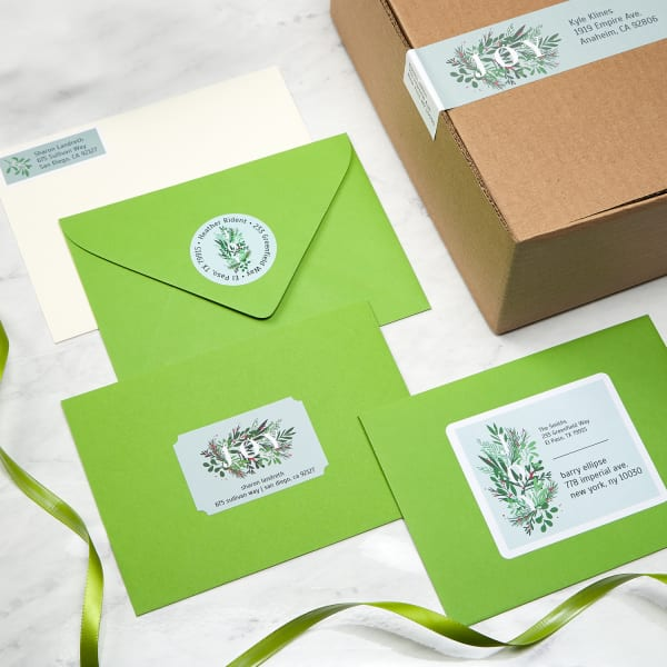three green envelopes and cardboard box decorated with four different shape and size labels with christmas theme
