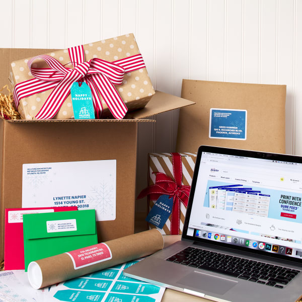 packages and letters with cute holiday mailing labels arranged around a laptop with avery design software displaying on screen