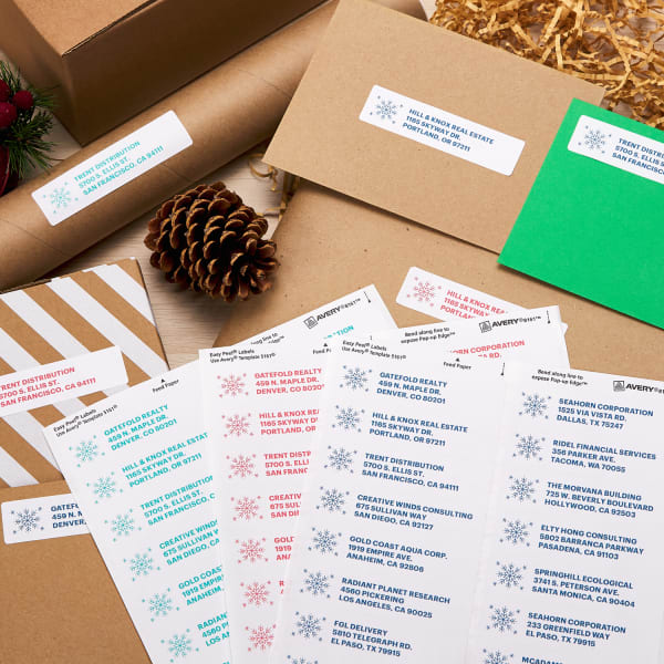 colorful christmas address label sheets and labels on envelopes and packages for holiday mailing arranged artistically with packing fill pine cones and apples