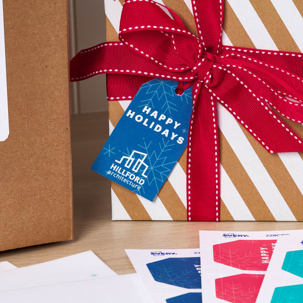 close up of custom holiday mailing gift tags shown on a wrapped gift and also printed on sheets arranged decoratively next to a box