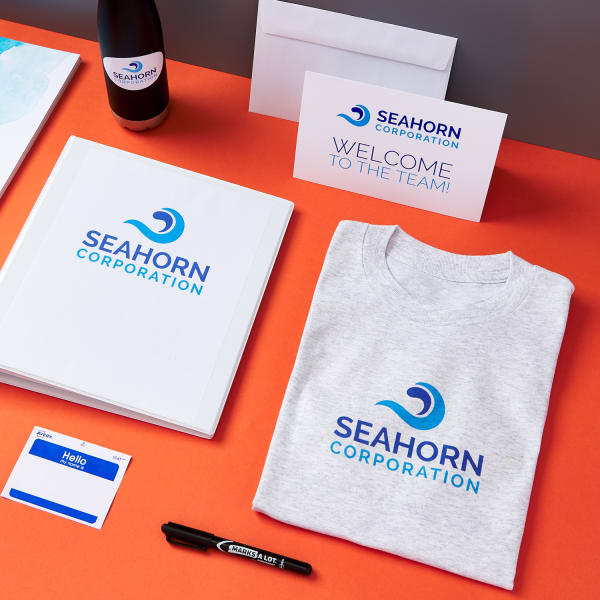 new hire branded onboarding materials and branded swag such as a name tag, a t-shirt, and a welcome card from Seahorn Corporation on bright orange table