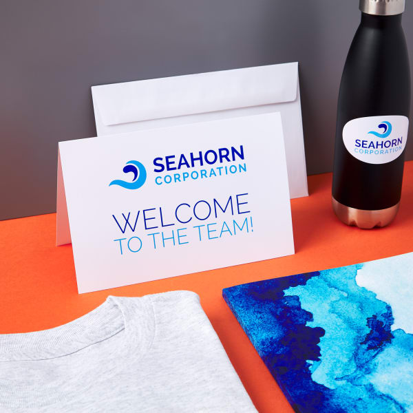 new hire branded onboarding welcome card from Seahorn Corporation on bright orange table