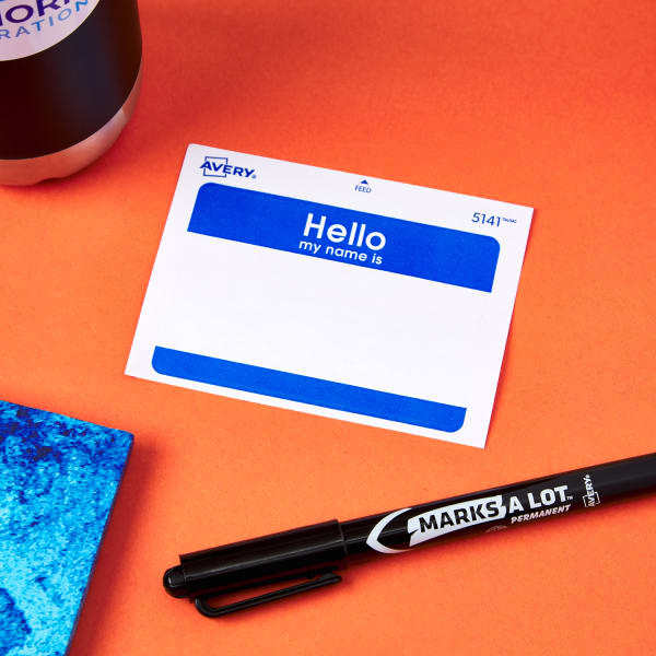 new hire name badge next to branded swag and Avery Marks-a-Lot permanent marker from Seahorn Corporation on bright orange table