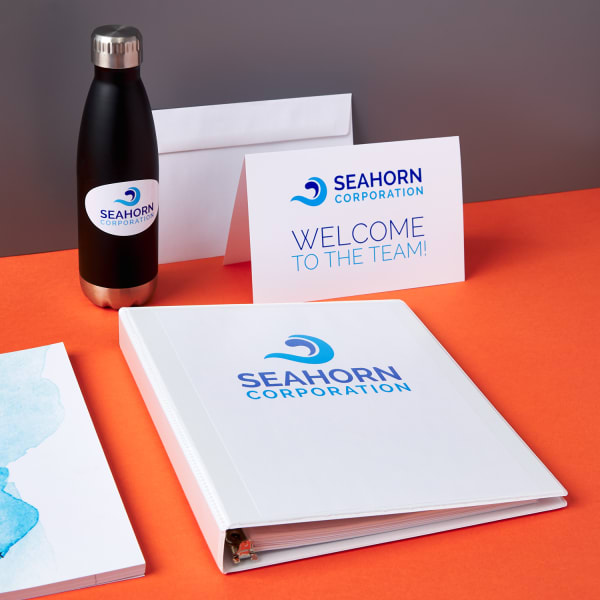 new hire branded onboarding materials and branded swag tumbler, binder, and welcome card from Seahorn Corporation on bright orange table